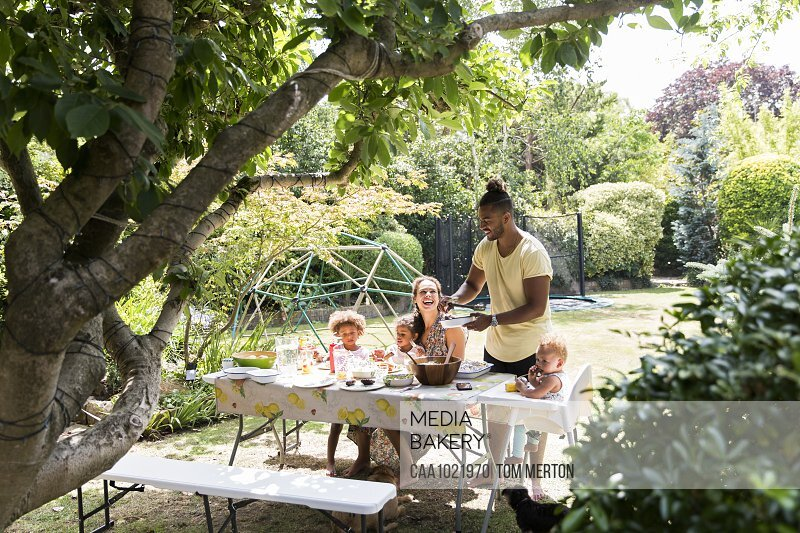 Father serving barbecue to family at summer backyard table