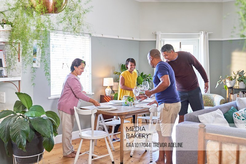 Mature couple friends setting dining table for lunch