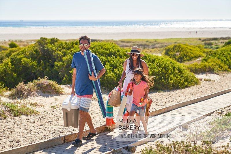 Happy family walking on sunny beach boardwalk