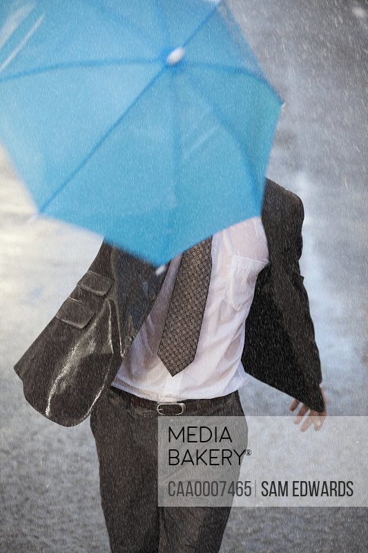 Photo by Caia Images - Businessman with tiny umbrella running in rainy  street