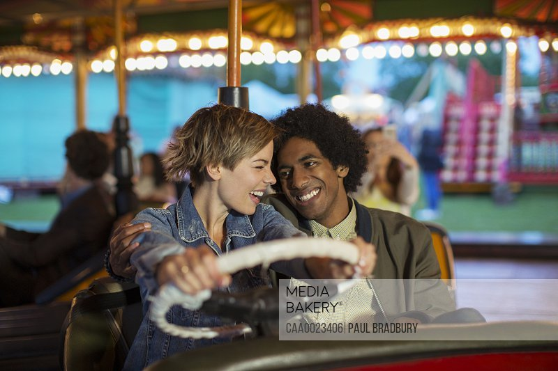 Young couple on bumper car ride in amusement park