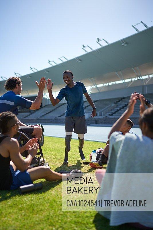 Male amputee and paraplegic athletes high fiving in sunny stadium