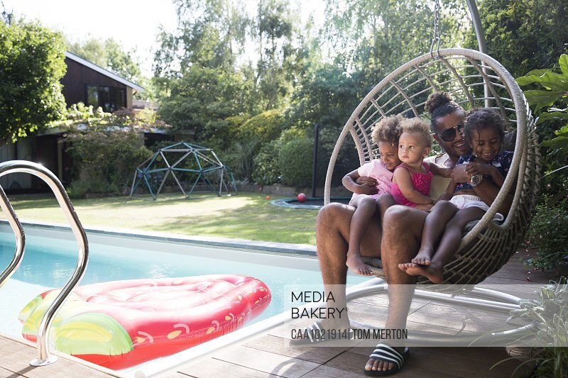 Happy father and daughters cuddling in summer poolside swing chair