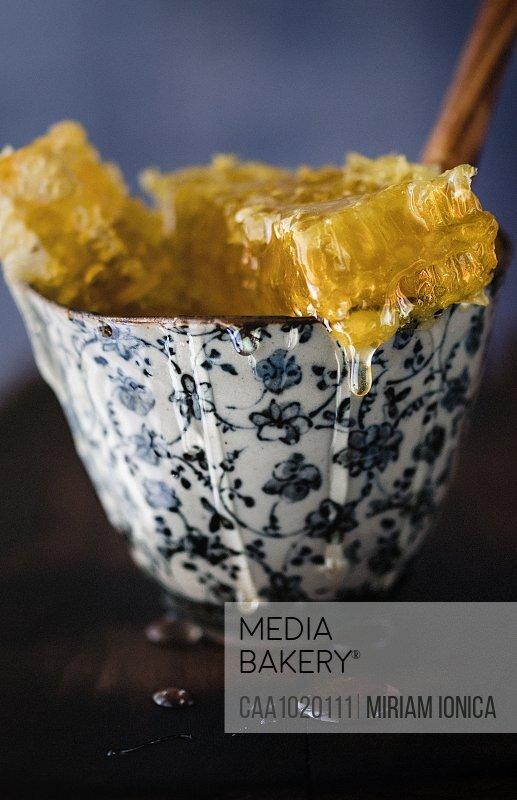 Close up dripping honeycomb in bowl