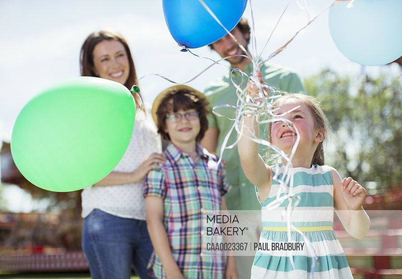 Young girl holding bunch of balloons family standing behind her
