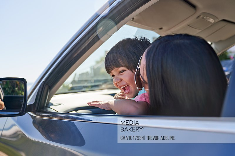 Happy mother and son in sunny car