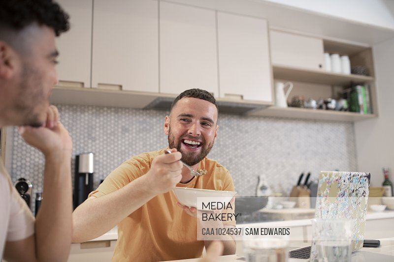 Happy gay male couple eating in kitchen