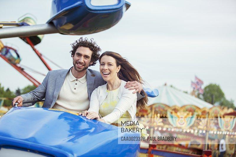 Couple enjoying ride on carousel in amusement park