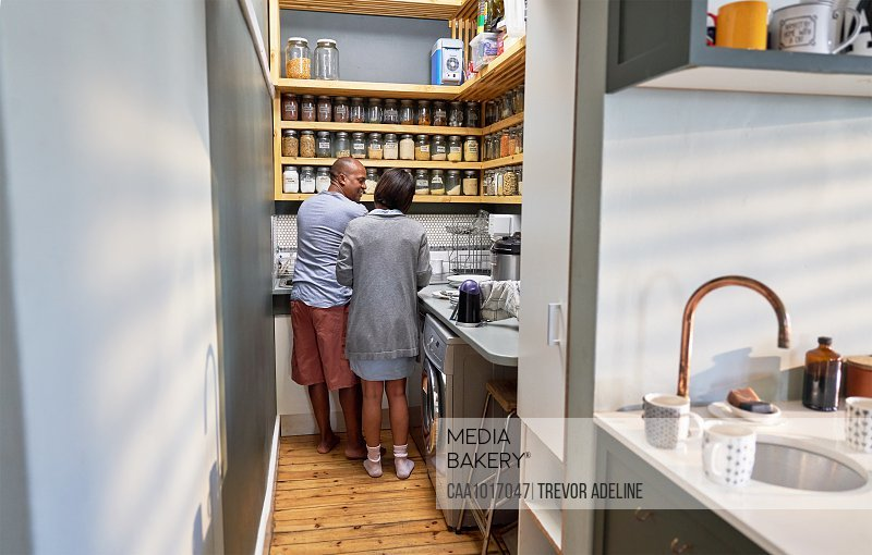 Couple talking and doing dishes in kitchen