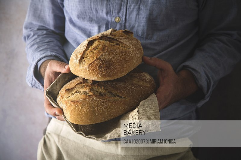 Close up man holding fresh home baked sourdough bread loaves