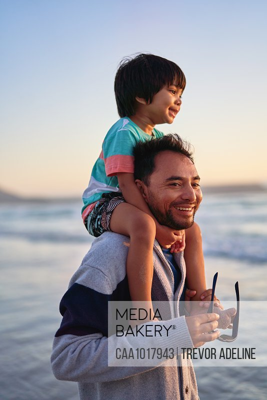 Happy father carrying son on shoulders on ocean beach