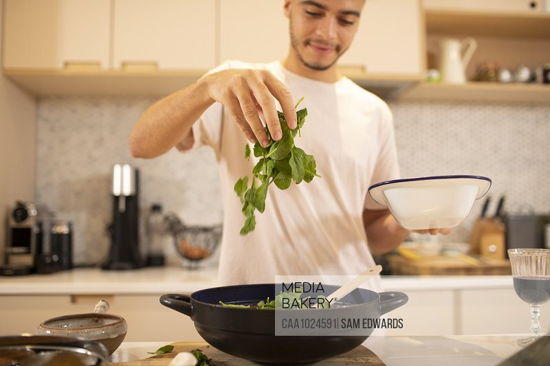 Young man cooking with fresh spinach in kitchen