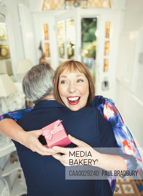 Surprise mature woman receiving gift from husband