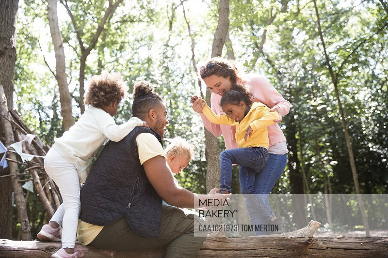 Happy family playing on fallen log in summer woods