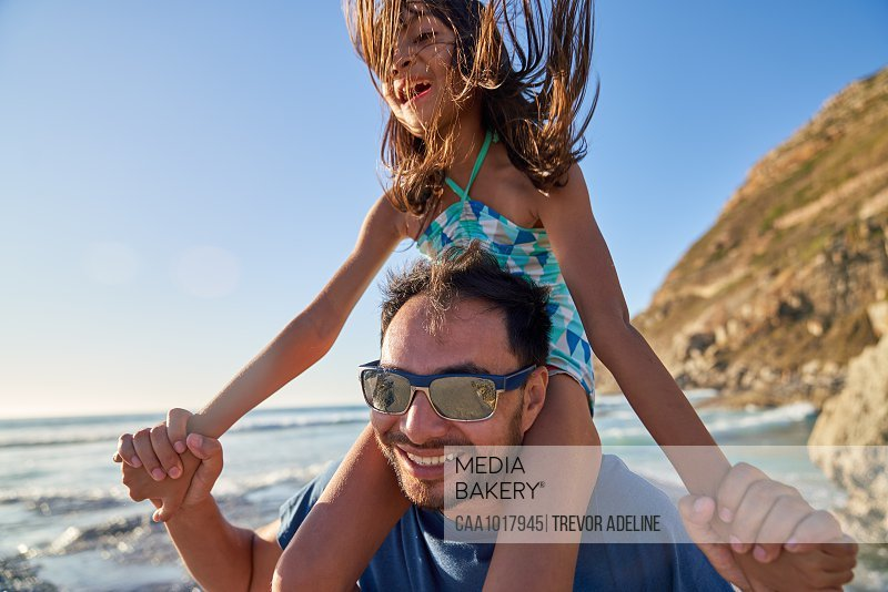 Happy father carrying daughter on shoulders on sunny beach
