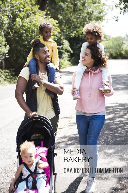 Happy family walking on sunny road