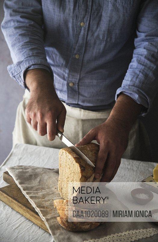 Man slicing fresh home baked sourdough bread loaf