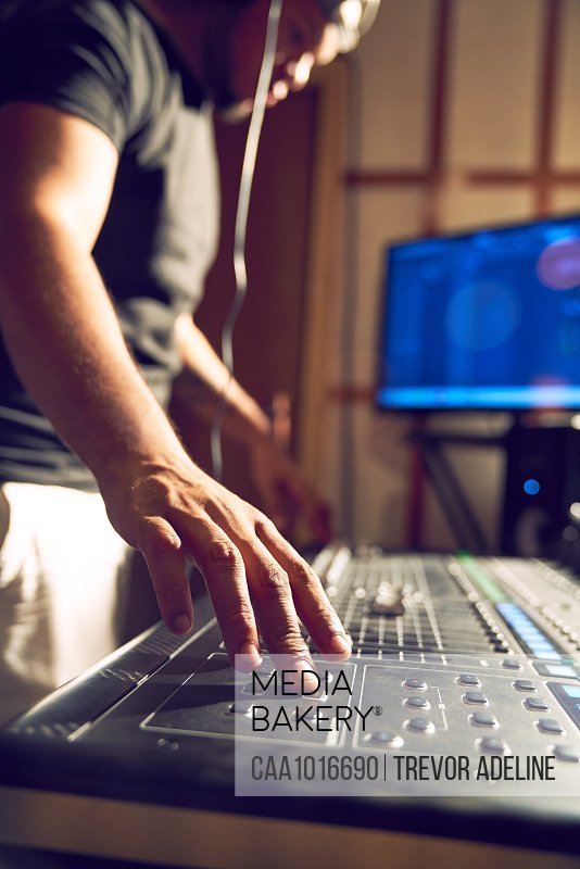 Man working at sound board in recording studio
