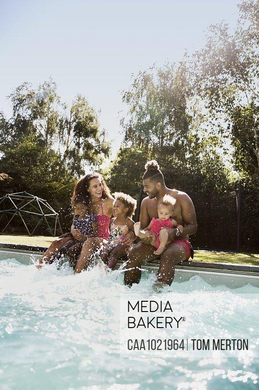 Happy family splashing at sunny summer poolside