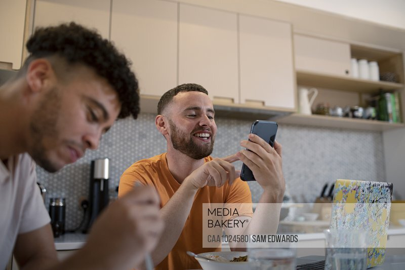 Happy gay male couple using smart phone and eating in kitchen