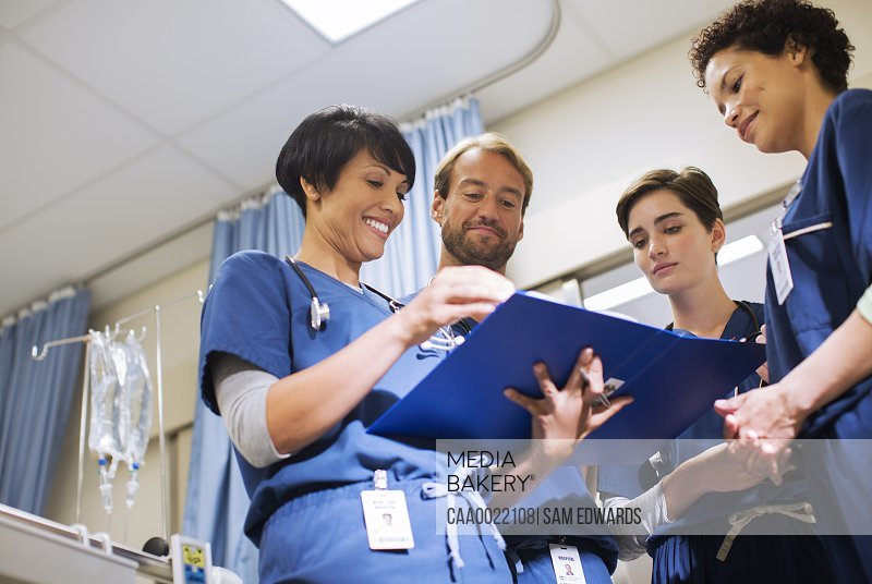 Doctors wearing scrubs looking at documents in hospital ward