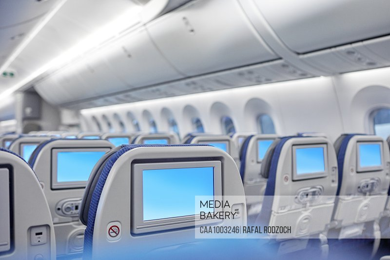 Entertainment screens on seats in airplane