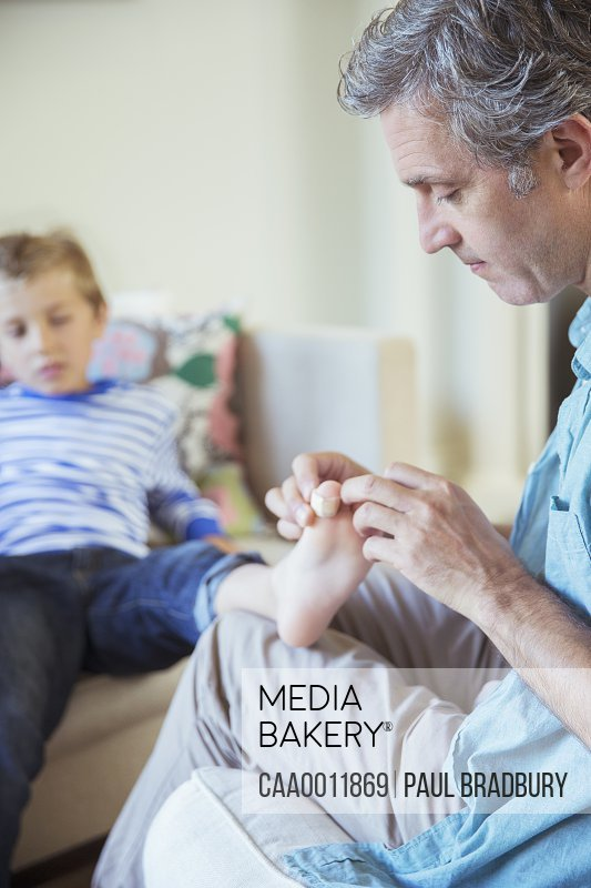 Father bandaging son's toe