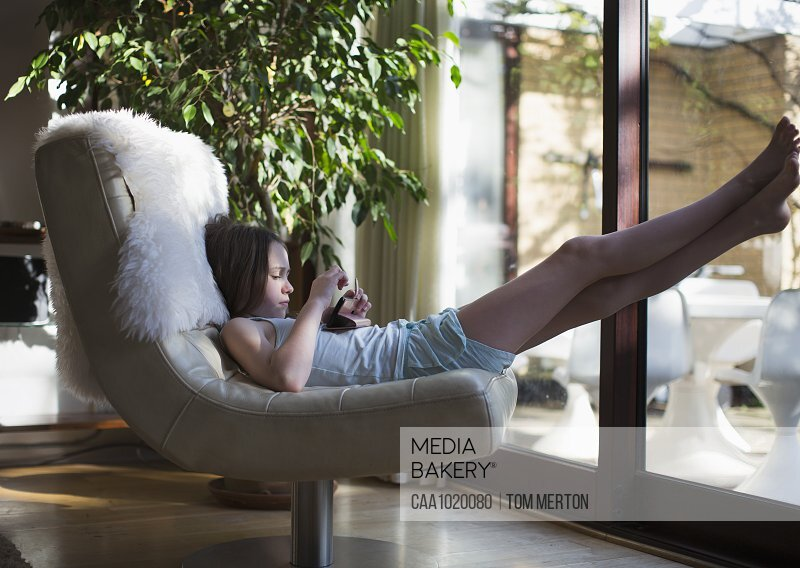 Girl with smart phone relaxing with feet up in living room