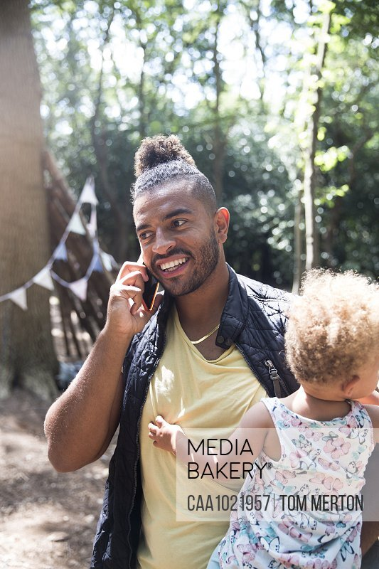 Smiling father holding toddler daughter and talking on smart phone