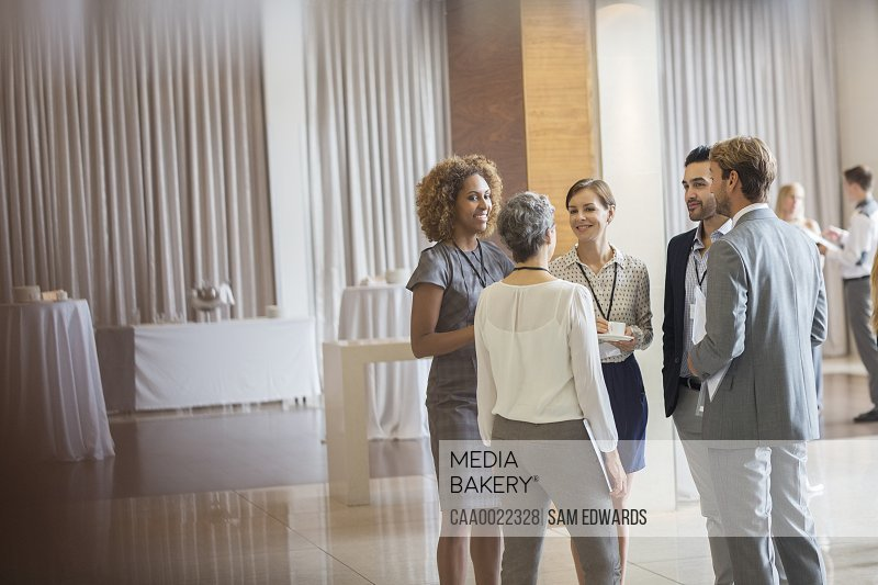 Business people standing in conference room talking and smiling