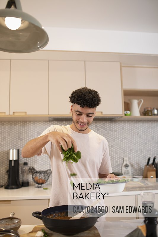 Smiling young man cooking with fresh basil in kitchen