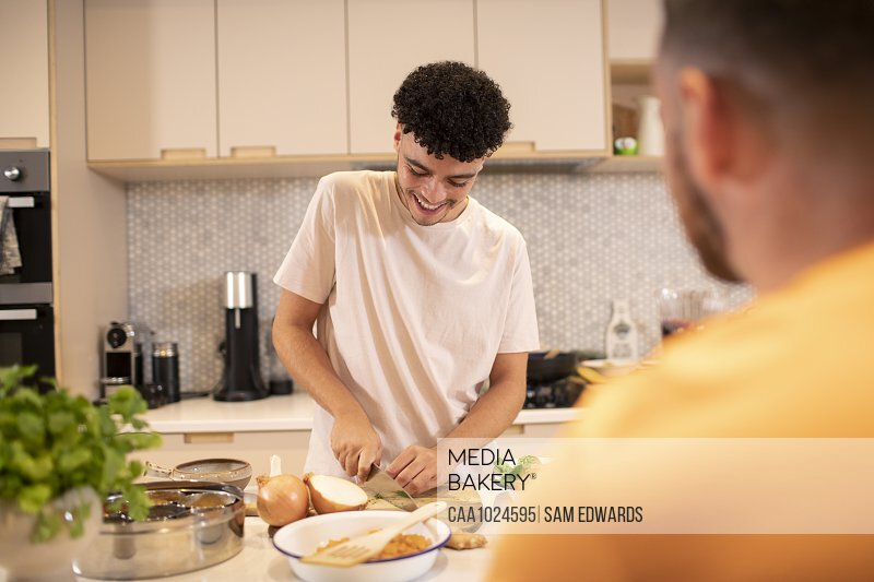 Young man cooking cutting onion in kitchen