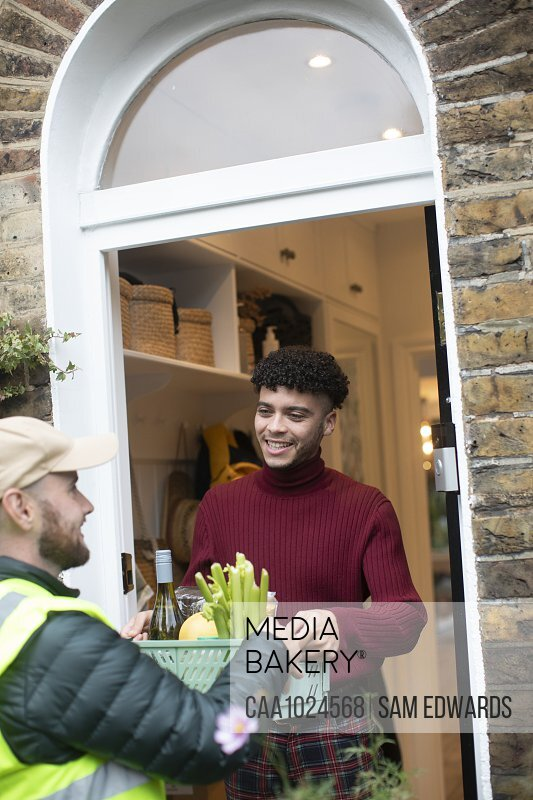 Man receiving grocery delivery from delivery man at front door