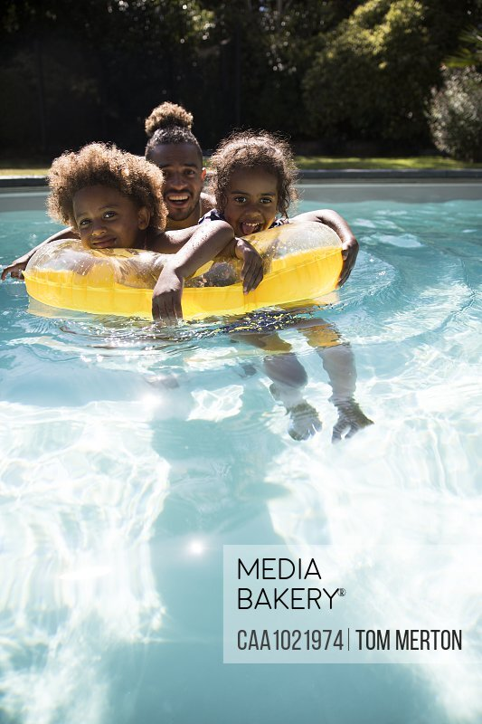 Portrait happy father and daughters in sunny summer swimming pool