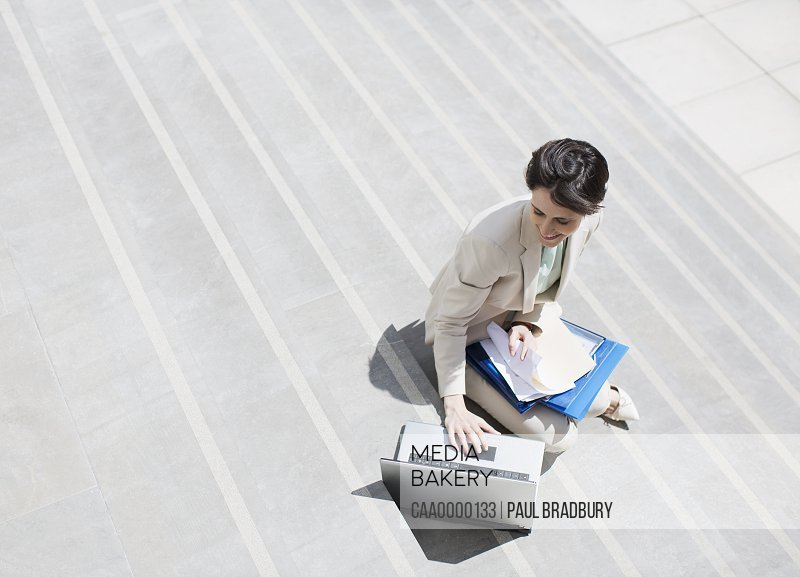 Businesswoman with paperwork using laptop on urban steps
