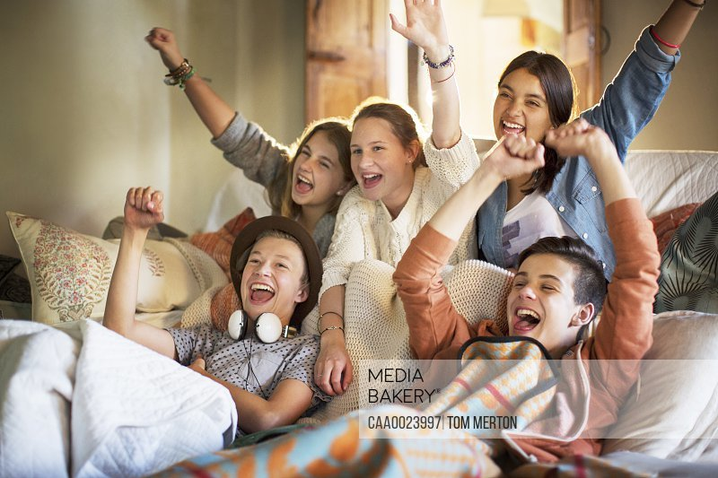 Group of teenagers having fun while watching tv on sofa
