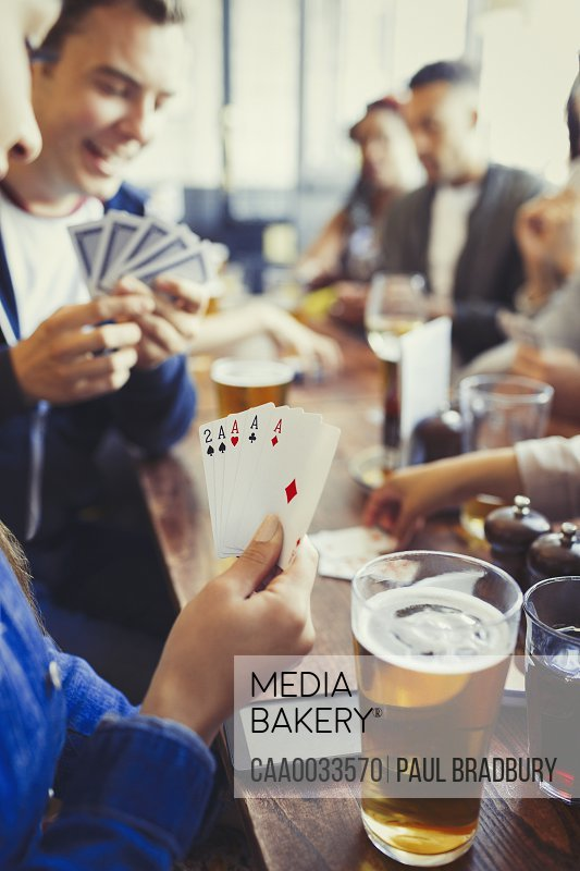 Woman holding aces four of a kind playing poker and drinking beer with friends at bar
