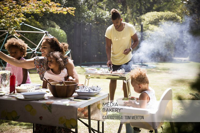 Family barbecuing and eating on sunny summer backyard patio
