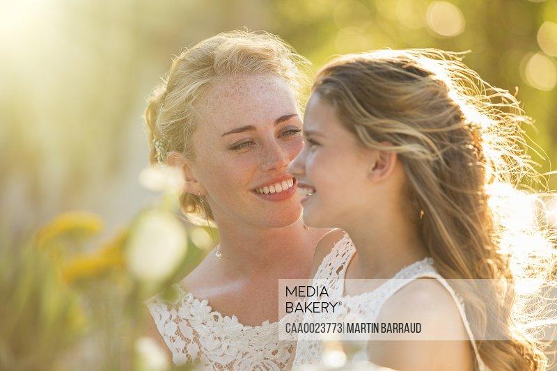 Bride talking to Bridesmaid in domestic garden