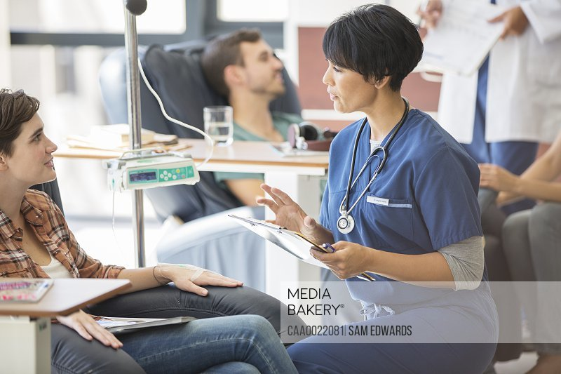 Doctor attending patients receiving intravenous infusion in hospital