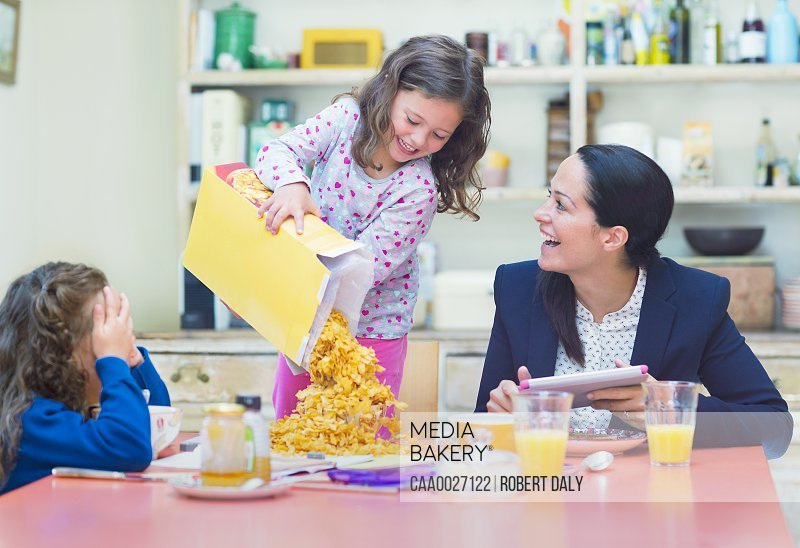 Playful girl pouring abundance of cereal onto breakfast table