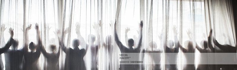 Silhouette of people raising hands behind transparent curtain