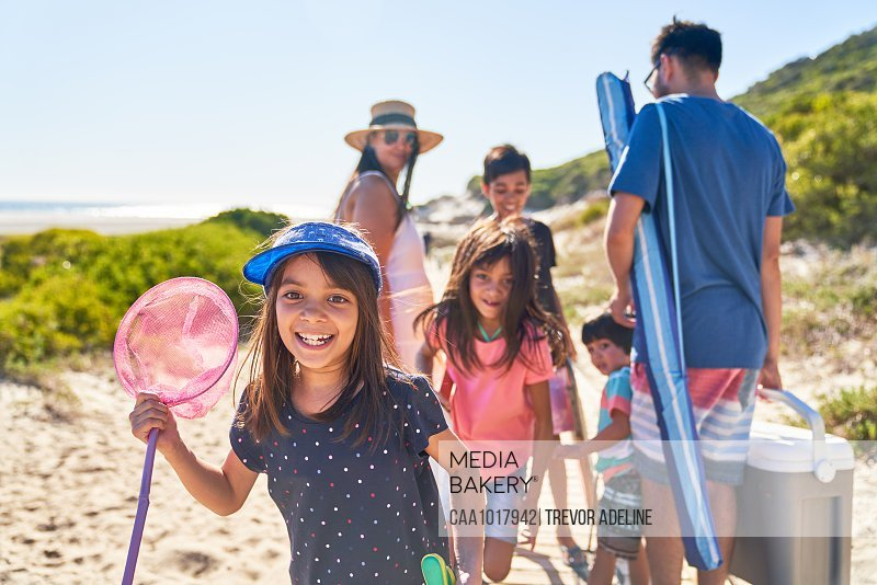 Portrait happy girl with butterfly net on sunny beach with family