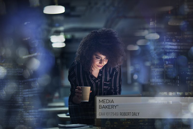 Businesswoman working late at laptop with coffee