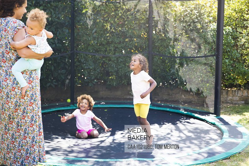 Happy mother and daughters playing on sunny backyard trampoline