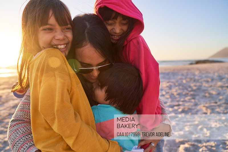 Happy mother and kids hugging on sunny beach