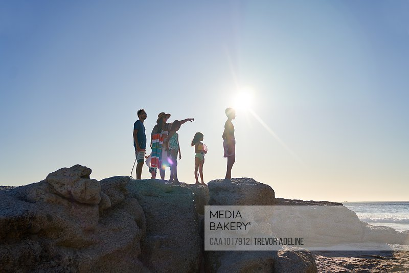 Family standing on rocks at sunny beach