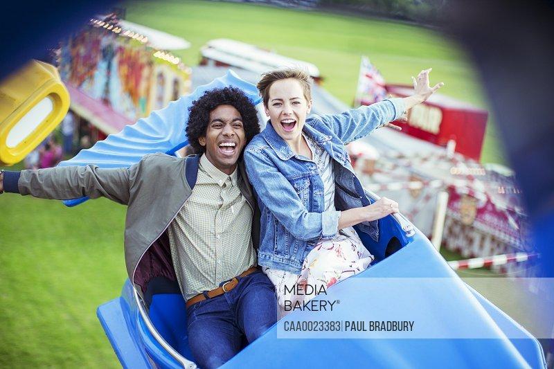 Cheerful couple having fun on carousel in amusement park