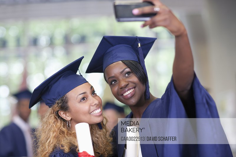 Two smiling female students taking selfie after graduation