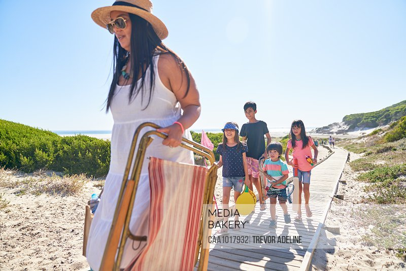 Family carrying folding chair and toys on sunny beach boardwalk